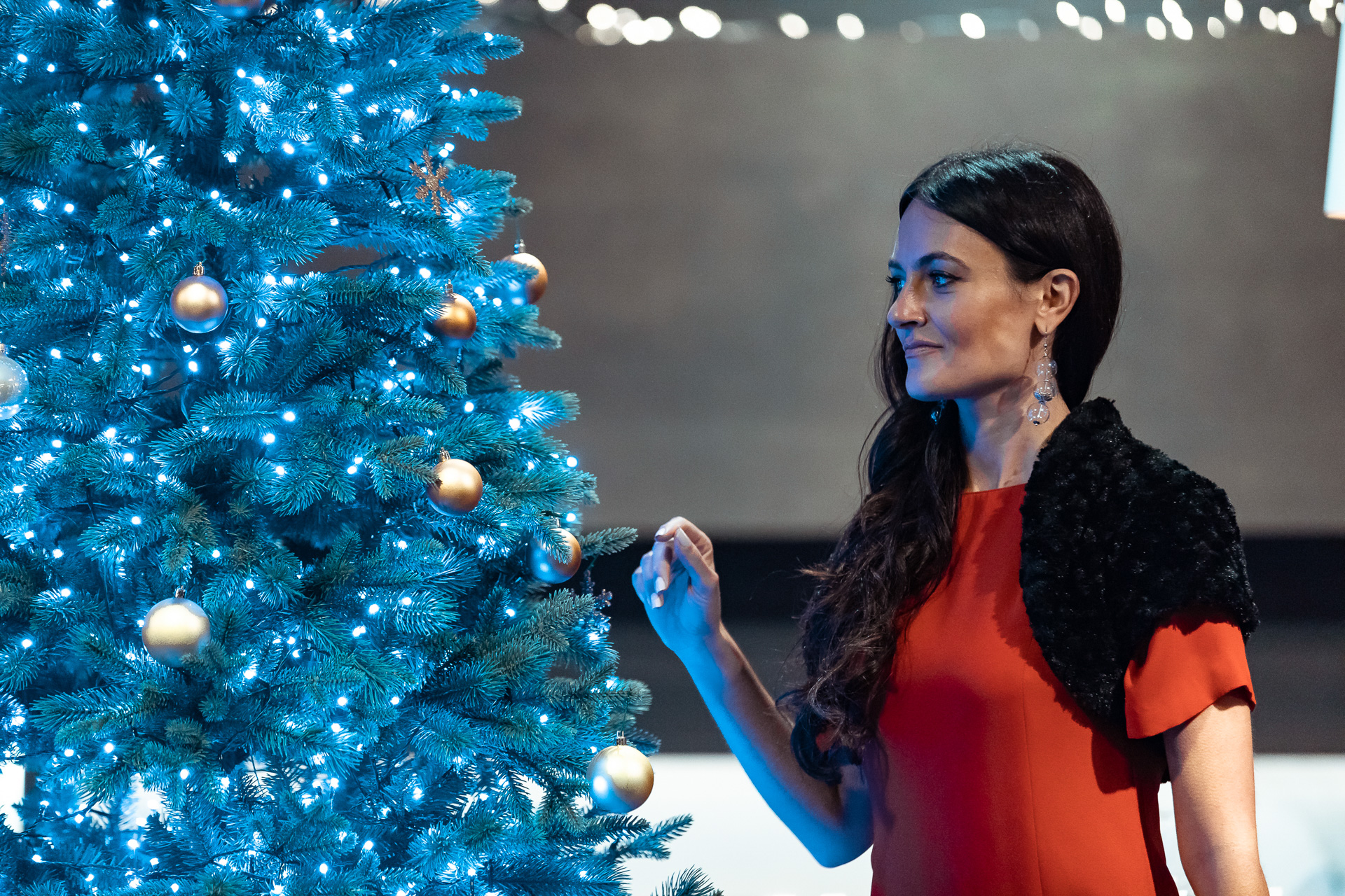 Attrice vicino all'albero decorato con luci azzurre durante le riprese del video commercial per Twinkly music